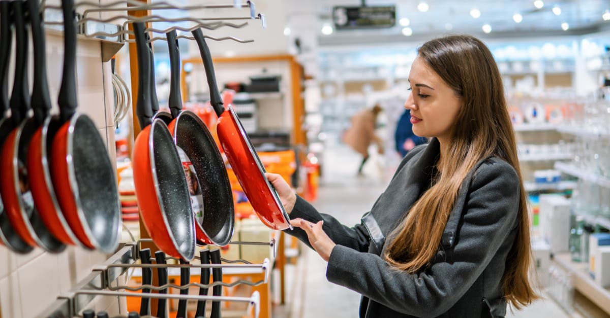 Mujer mirando sartenes en comercio